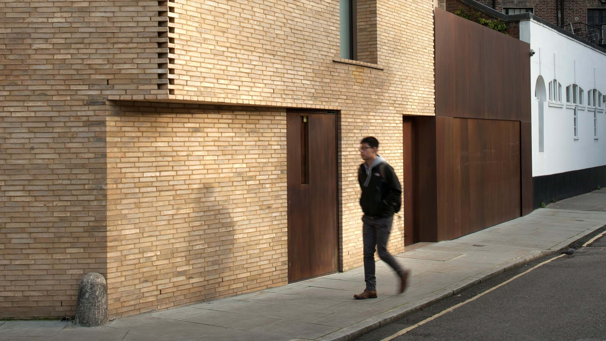 Man passing brick house